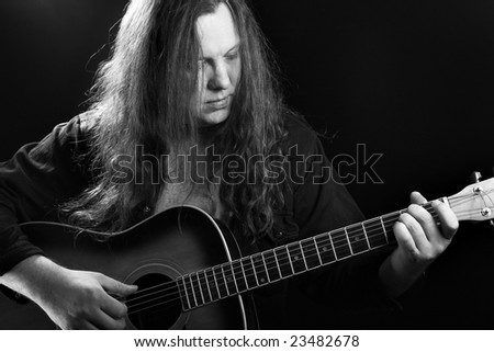 Man playing acoustic guitar, black and white image - stock photo