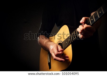 Man playing acoustic guitar in low light environment. Acoustic guitarist concert, unplugged performance.