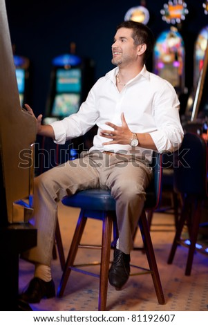 man playing at slot in casino - stock photo