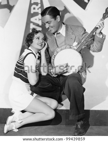 Man playing banjo for adoring woman - stock photo