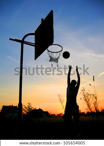 Man playing basketball - dark silhouette - stock photo