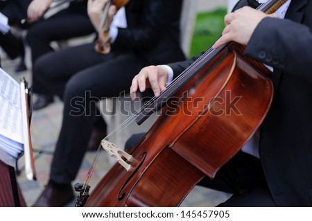 man playing cello in restaurant's yard - stock photo