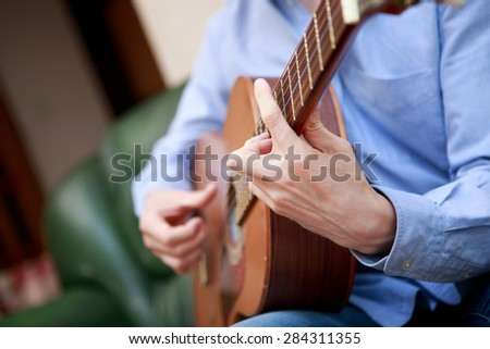 Man playing classic, acoustic guitar - stock photo