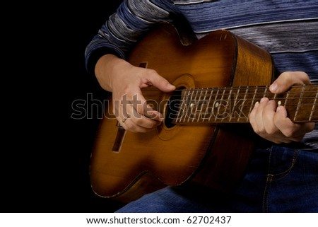 man playing classical guitar at black background - stock photo