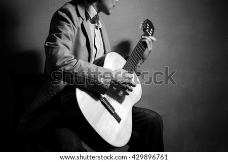 Man playing classical guitar. Black and white photo. - stock photo
