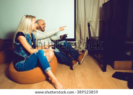 Man playing computer games and having some fun with beautiful woman. concept of leisure entertainment and fun - stock photo