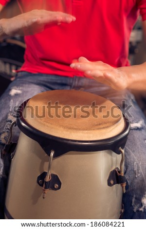 Man playing Cuban drum by his hands - stock photo