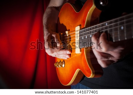 Man playing electric guitar at red background - stock photo