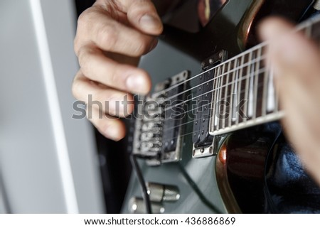man playing electric guitar close up view, very shallow depth of field image - stock photo