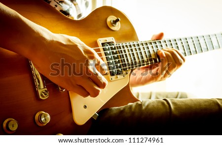 man playing electric guitar with nature light - stock photo