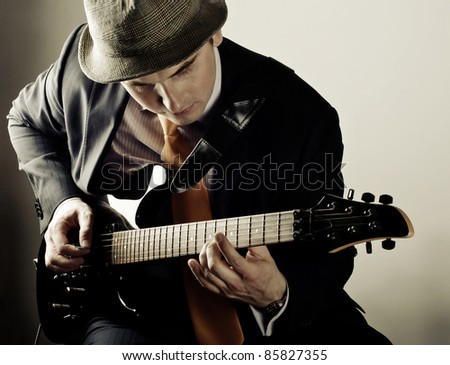man playing electrical guitar in sepia