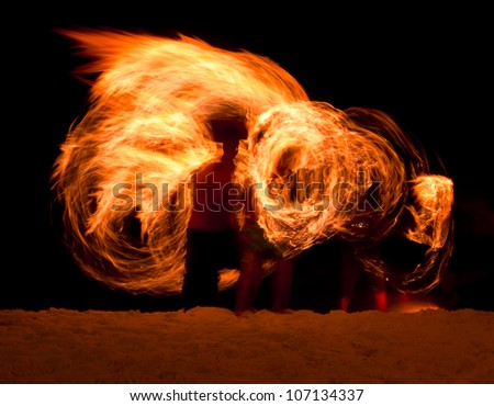 Man playing fire poi on the beach