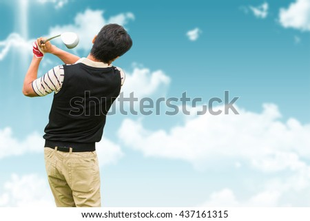 Man playing golf against blue sky - stock photo