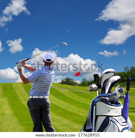 Man playing golf against blue sky with golf bag - stock photo