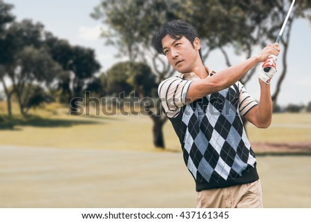 Man playing golf against view of a park - stock photo