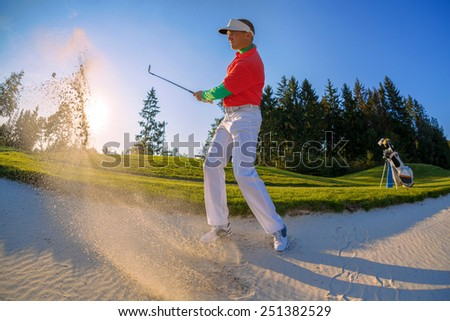Man playing golf from bunker  against sunset - stock photo