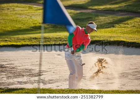 Man playing golf from the bunker - stock photo