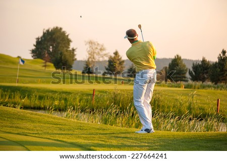 Man playing golf in the evening - stock photo