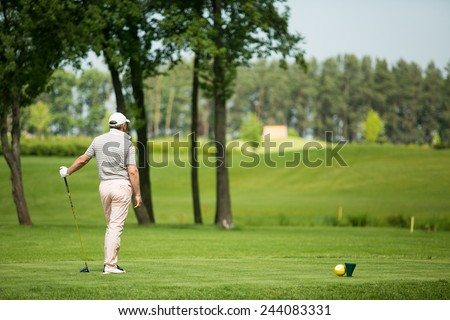Man playing golf on beautiful sunny green golf course - stock photo