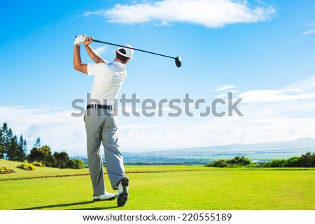 Man Playing Golf on Beautiful Sunny Green Golf Course. Hitting Golf Ball down the Fairway from the Tee with Driver.  - stock photo