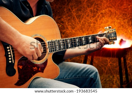 man playing guitar against fire background - stock photo