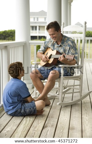 Man playing guitar as a boy listens on the front porch of his home. Vertical shot. - stock photo