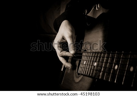 man playing guitar at black background - stock photo