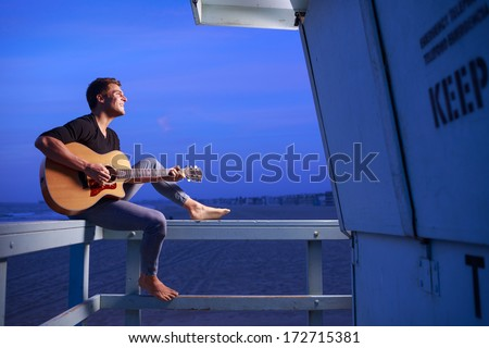 Man playing guitar at dusk beach - stock photo