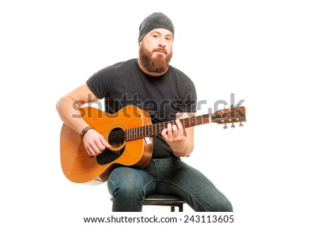 Man playing guitar. Bearded young men sitting and playing acoustic guitar over white - stock photo