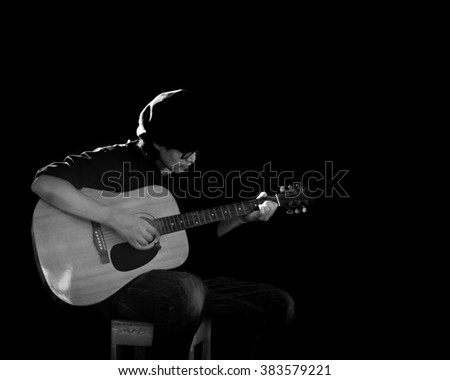 Man playing guitar., Black and white photo with open space.