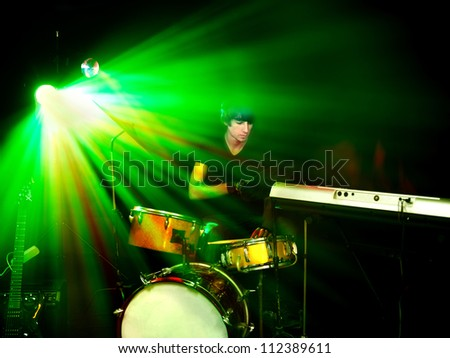 Man playing  guitar in night club. Lighting effects.