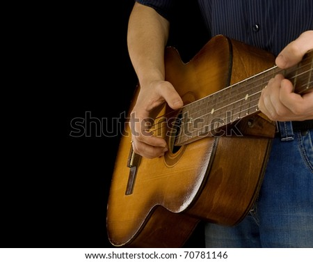 man playing guitar isolated on black background - stock photo
