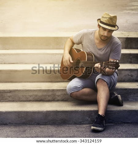 Man playing guitar on the street - stock photo