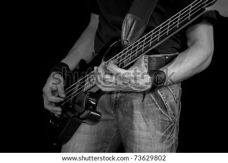 man playing his bass guitar, black and white