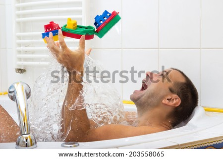 man playing in the bath with steamer - stock photo