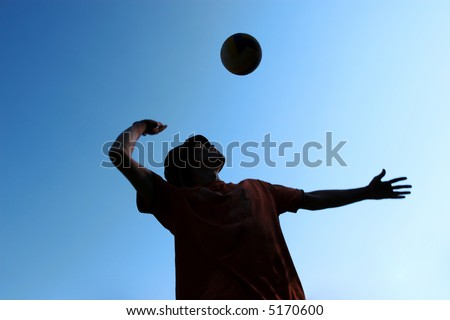 man playing in volleyball and ball above him