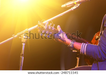 man playing music by wooden acoustic guitar in the concert stage - stock photo