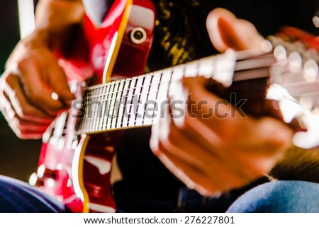 Man playing music with a guitar (focus on strings) (film-like added noise) - stock photo