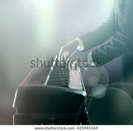 Man playing on electronic musical keyboard, close-up. - stock photo