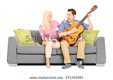 Man playing on guitar with his girlfriend sitting on sofa isolated on white background - stock photo