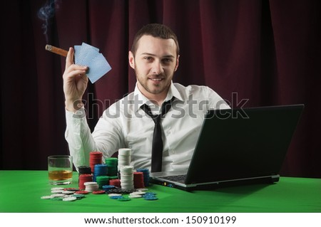 Man playing on line poker - stock photo
