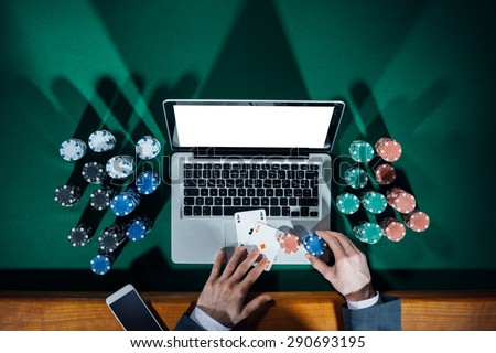 Man playing online poker with laptop on a green table with chips all around, top view - stock photo