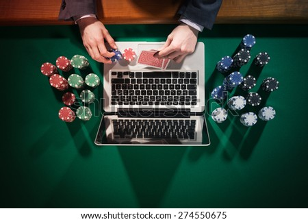 Man playing online poker with laptop on a green table with chips all around top view, he is looking at his cards - stock photo