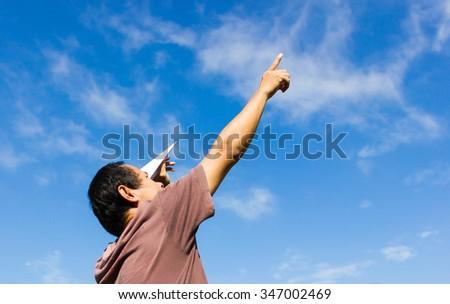 Man playing paper airplane. - stock photo