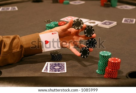 Man playing poker and performing a chip trick with ace up sleeve - stock photo