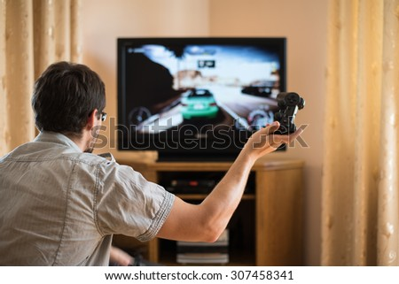 man playing racing video game on console (television) in home - stock photo