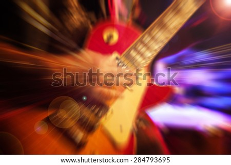 man playing rock guitar on concert - stock photo