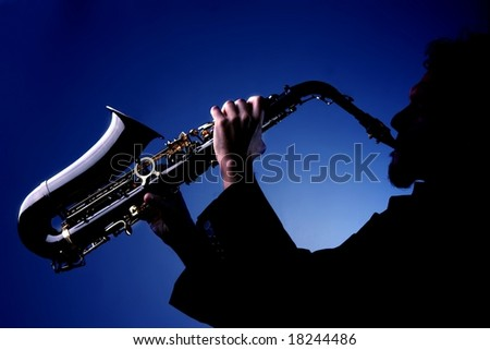 Man playing sax in silhouette - stock photo