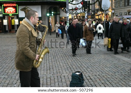 Man playing saxophone a shoppingstreet in Copenhagen, Denmark - stock photo