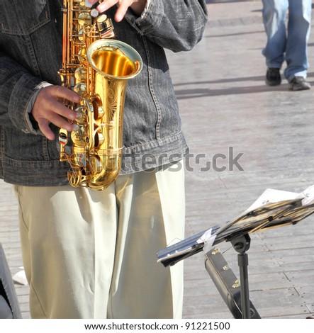 Man playing saxophone on the street - stock photo